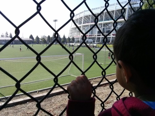 "Saturday afternoon walk - we went all the way to the stadium. Then up the stairs at the train station and down the dirt hill to this fence. I explained what the boys in the green shirts and the pink shirts were doing. You said, ""One day I will kick the ball up high in the sky and into the net."""